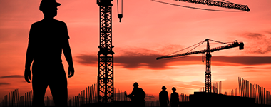 construction site with cranes in silhouette